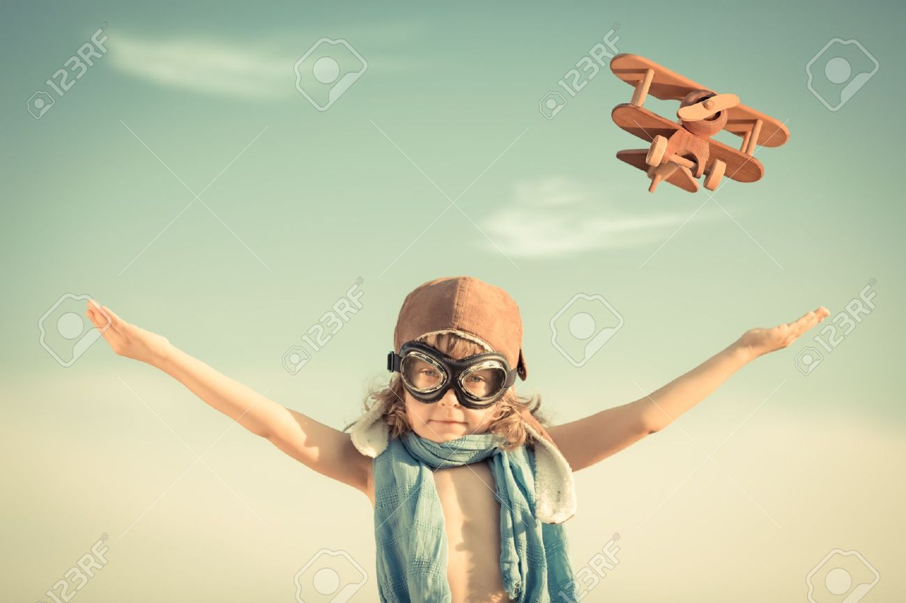 20409576-happy-kid-playing-with-toy-airplane-against-blue-summer-sky-background-stock-photo
